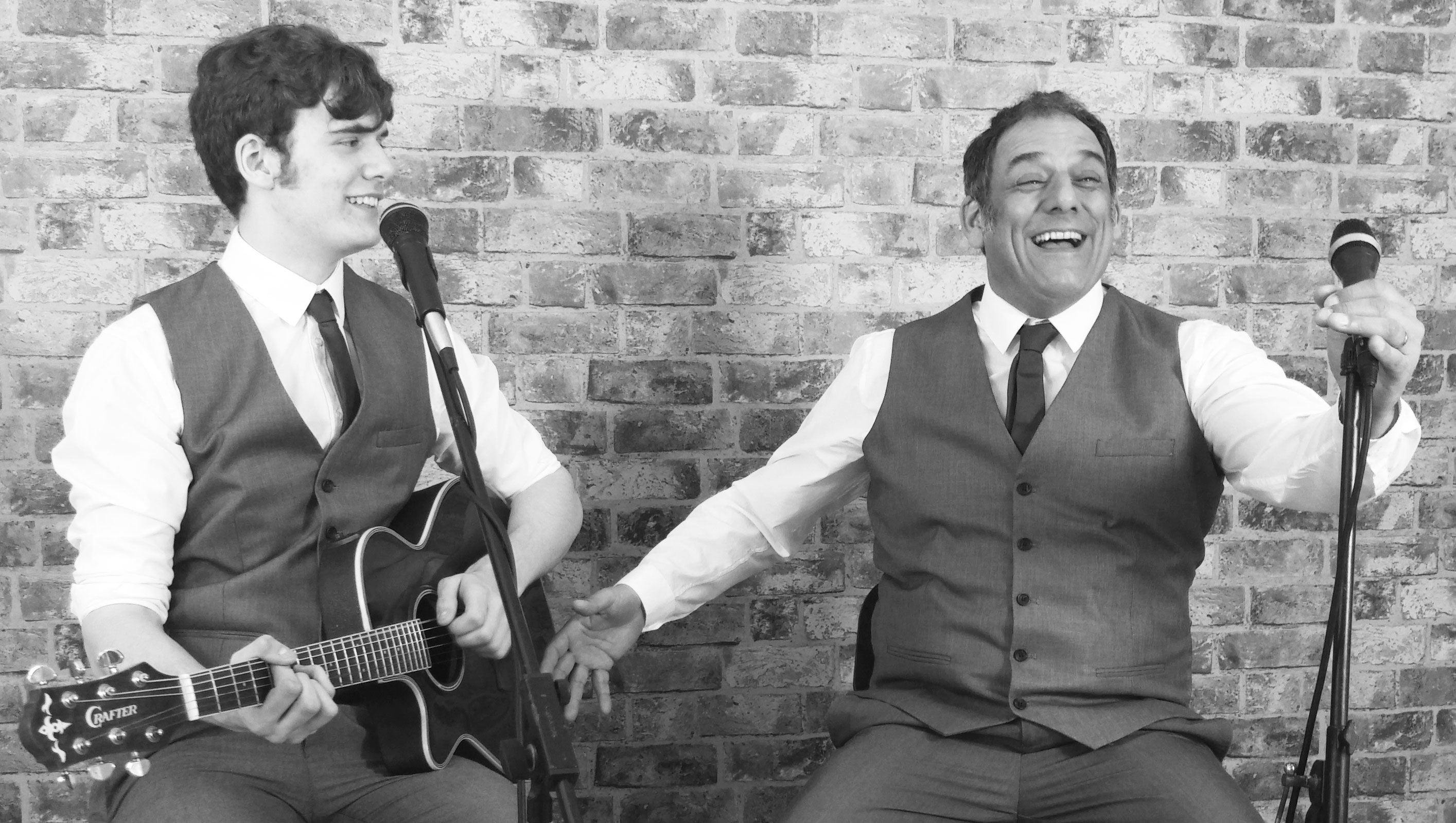 Nottingham acoustic duo Eastbound and Down sat on chairs wearing white shirt, dark tie and grey waistcoat. Guitar held by Jack