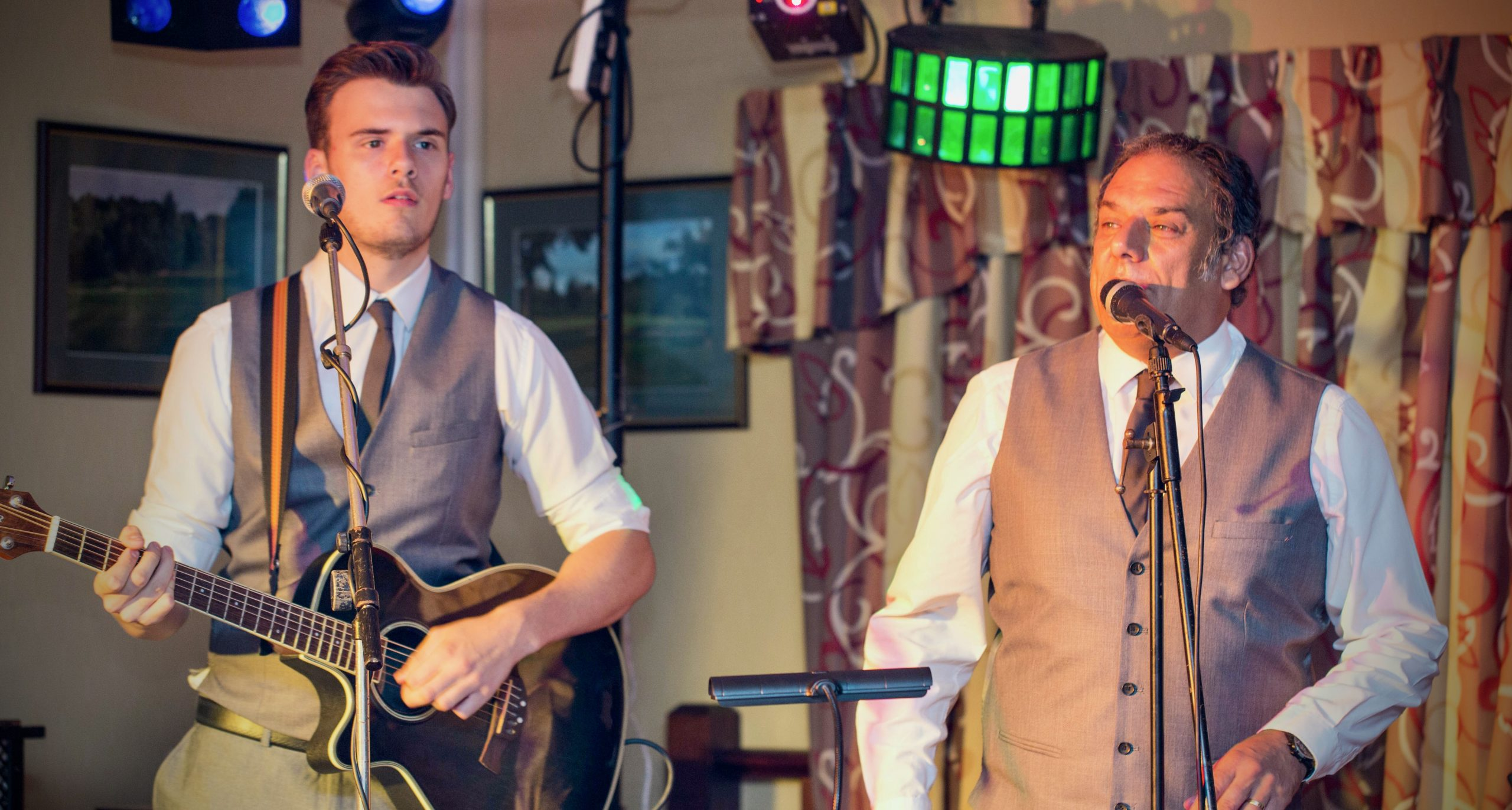Acoustic Duo Eastbound and Down on stage singing into microphones dressed in white shirts, dark tie and grey waistcoats Jack is playing a guitar